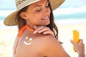Woman sat on the beach applying sun cream