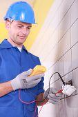 electricista está comprobando una toma de corriente con un amperímetro
