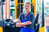 Hardware store employee in warehouse for home improvement equipment with forklift poster