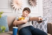 Overweight boy watching TV with snacks indoors poster