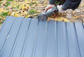Roofer Cutting Metal Roof Sheets, Metal Tile  For House Roofing Construction. Cut Metal Tile Roof. poster