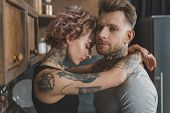 View Of Young Tattooed Couple Embracing In Kitchen poster