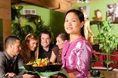 Young people eating in a Thai restaurant; the waitress brings the dishes, rice and others