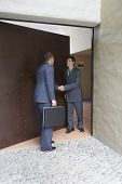 Hispanic businessman being greeted in doorway