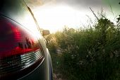 Backlighting Image Of A Car Rear Light Reservation With A Bright Morning Green Meadow poster