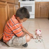 picture of thinkers pose  - Hispanic boy counting money on floor - JPG