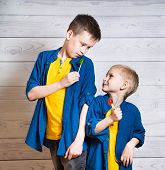 Portrait Of Two Beautiful Boys In Yellow T-shirts And Denim Jackets, Shirts. Boys Are Standing On A  poster