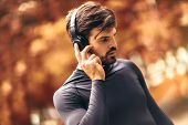 Portrait Of  Young Man On A Morning Jogging In The Autumn Park, Man Listening To Music With Headphon poster