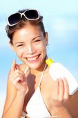 Vacation woman putting sunscreen on nose on beach. Cute beautiful young woman on summer holiday enjoying the sun on sunny summer day. Multiracial Asian / Caucasian girl.