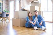 Young beautiful couple in love moving to new home, sitting on the floor very happy and cheerful for  poster