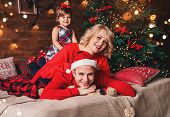 Family In Christmas Santa Hats Lying On Bed. Mother, Father And Baby Having Fun In Living Room Decor poster