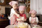 Three Little Chefs Enjoying In The Kitchen Making Big Mess. Little Girls Making Bread In The Kitchen