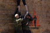 POCONO MANOR, PA - APR 29: An entrant gets help to get up and over the Berlin Walls obstacle at Toug