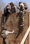 POCONO MANOR, PA - APR 29: A participant gets help up and over the Berlin Walls obstacle at Tough Mudder on April 29, 2012 in Pocono Manor, PA.  The course is designed by British Special Forces.