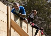 POCONO MANOR, PA - APR 28: A man pulls himself up and over the Berlin Walls obstacle at Tough Mudder