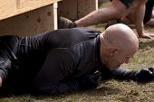 POCONO MANOR, PA - APR 28: A man crawls under an obstacle at Tough Mudder on April 28, 2012 in Pocon