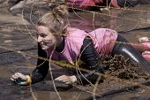 POCONO MANOR, PA - APR 29: A woman crawls through water under electrified wires at Tough Mudder on A