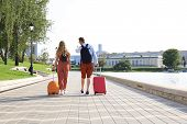 Rear View Of Tourist Couple Holding Hands And Dragging Luggage, Sightseeing Visiting Street, Outdoor poster