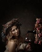 Attractive Woman With Glass Of Red Wine In Wine Cellar . Vine Wreath With Blue Grapes On A Head. Red poster