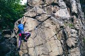 The Girl Climbs The Granite Rock. Rock Climber Trains On Natural Terrain. Extreme Hobby. poster