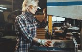 Middle Aged Woman Working With A Drill In Workshop. Concept Of Woman In A Male-dominated Profession, poster
