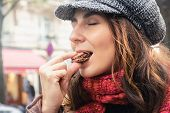 Woman Eating Chocolate Food On Street In Paris In Vacation. Woman Eating Food In Vacation In Paris.  poster