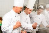 Two male cooks working in professional industrial kitchen prepare food