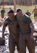 POCONO MANOR, PA - APR 29: Muddy participants come through an obstacle with electrified wires at Tou