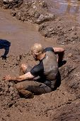 POCONO MANOR, PA - APR 29: A man slides into a pit of mud and water at Tough Mudder on April 29, 201