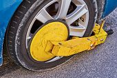 Clamped Front Wheel Of Illegally Parked Car, Yellow Clamp Attached To Wheel poster