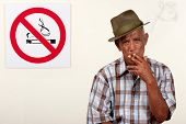 stock photo of scant  - A senior citizen pays scant regard to a non - JPG
