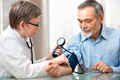 image of observed  - doctor measuring blood pressure of male patient - JPG