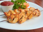 foto of souse  - Grilled chicken on a skewer on white plate