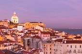 stock photo of red roof  - Panorama of old traditional city of Lisbon with red roofs and view of river Tagus at sunset - JPG