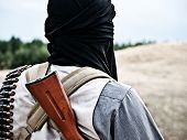 stock photo of rebel  - Muslim rebel with automatic rifle and machine-gun belt