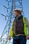 stock photo of lineman  - Man in front of an electricity pylon - JPG