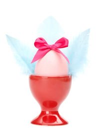 image of chucky  - Colored easter egg with pink bow and blue wings in red egg cup - JPG