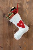 White Christmas stocking filled with traditional gifts and toys hanging by a rusty nail in an old door.