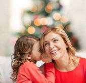 christmas, x-mas, winter, happiness concept - mother and daughter whispering gossip
