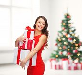 christmas, x-mas, valentine's day, celebration concept - smiling woman in red dress with many gift b