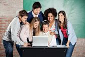 Portrait of female students standing with classmates while teacher teaching on laptop in classroom