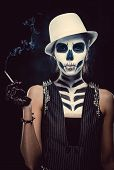 Woman With Skeleton Face Art Smoking Over Black Background, Conceptual Photo