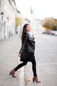 Fashion woman in city wearing urban leather jacket. Stylish female model walking in street crossing