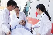 stock photo of stretcher  - Three doctors wheeling in elderly patient on stretcher - JPG