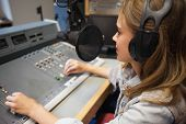 Focused pretty radio host moderating sitting in studio at college