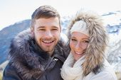 Close-up portrait of a loving couple in jackets in front of snowed mountain range