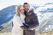 Portrait of a loving young couple in fur hood jackets against snowed mountain range