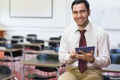 Portrait of a smiling teacher with tablet PC in the class room