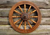 Spinning Wheel On The Log House Wall