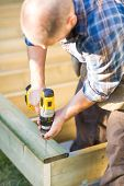 Carpenter using cordless drill while building deck